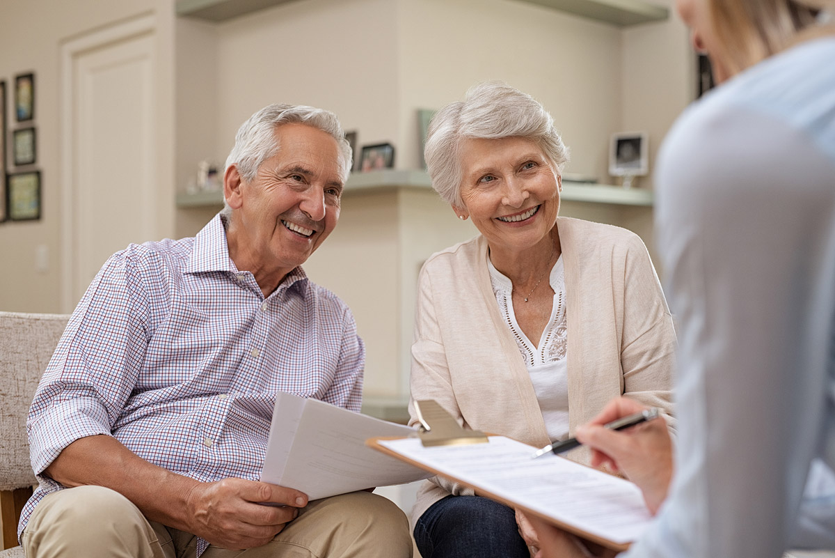An elderly couple discussing estate planning with local lawyers